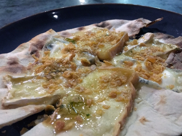 baked cheeses with nuts and honey on flatbread at temper